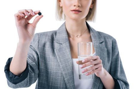 cropped view of woman holding glass of water and activated carbon tablet, isolated on white
