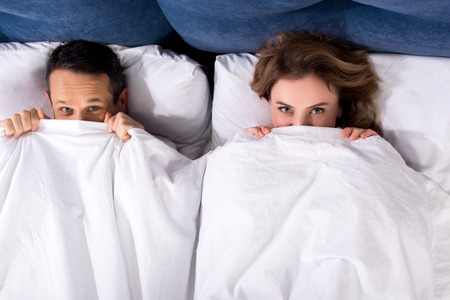overhead view of wife and husband hiding under blanket while lying in bed at home Standard-Bild - 114332462