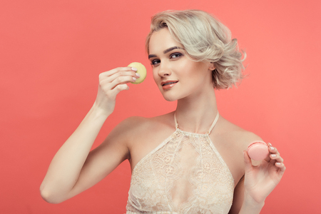 beautiful blonde woman with two delicious macarons, isolated on red