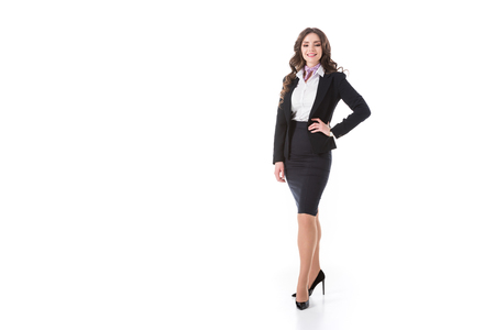 attractive stewardess standing with arm akimbo isolated on white