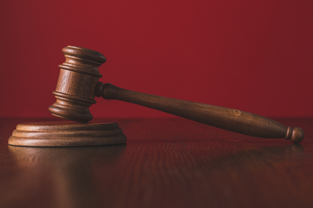 judgments gavel on wooden table infront of red background, law concept Stock Photo