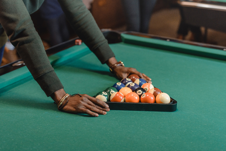 cropped image of male hands forming set of billiard balls by triangle Banco de Imagens