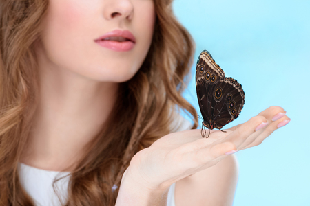 cropped shot of beautiful young woman with butterfly on hand isolated on blue