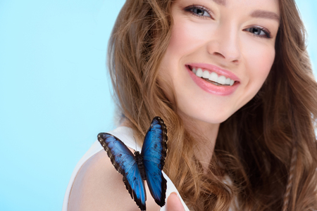 smiling young woman with butterfly on shoulder isolated on blue 写真素材
