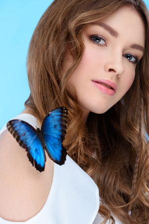 attractive young woman with butterfly on shoulder isolated on blue