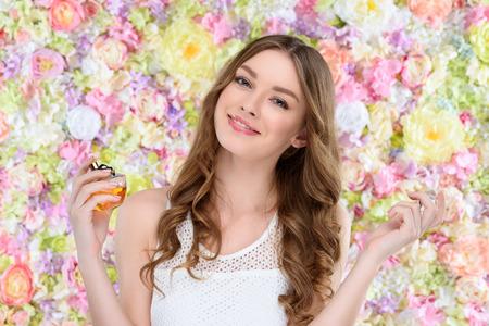 Hermosa joven rociar perfume sobre fondo floral