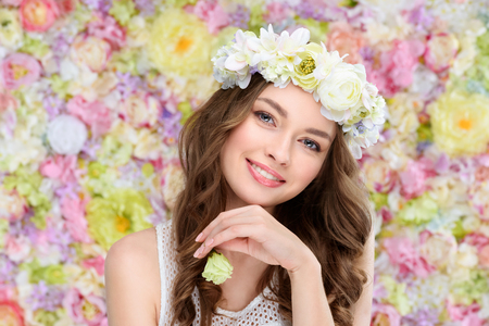 smiling young woman in floral wreath with blossoming rose bud
