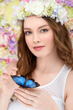smiling young woman in floral wreath with butterfly on hand Stock Photo
