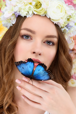 close-up portrait of sensual young woman in floral wreath with butterfly on hand Stock Photo