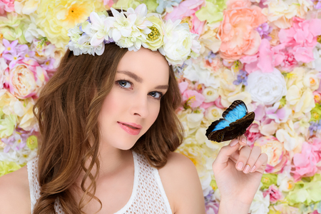 young woman in floral wreath with butterfly on hand Stock Photo