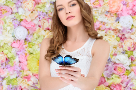 attractive young woman in floral wreath with butterfly on hand 写真素材