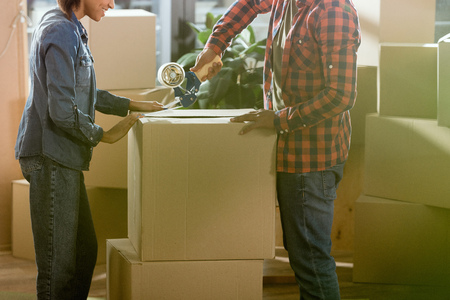 cropped view of african american couple packing cardboard box to move in new home