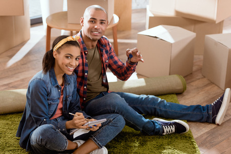 african american couple with keys and notepad sitting in new apartment
