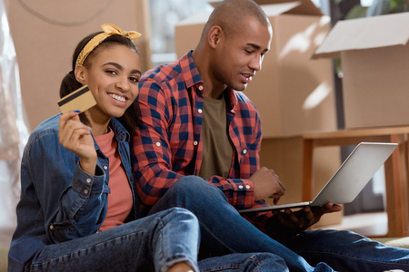 african american couple shopping online with credit card and laptop in new apartment