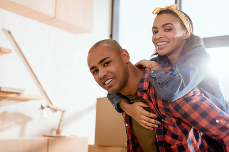 happy african american couple piggybacking in new home