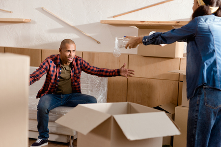 african american couple packing and quarreling in new apartment with cardboard boxes Stock Photo