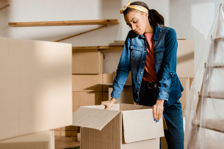 upset african american girl unpacking cardboard boxes in new apartment