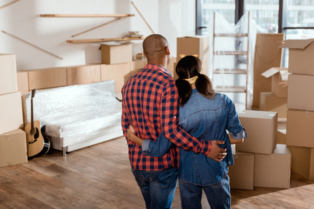 back view of african american couple looking at new home with cardboard boxes