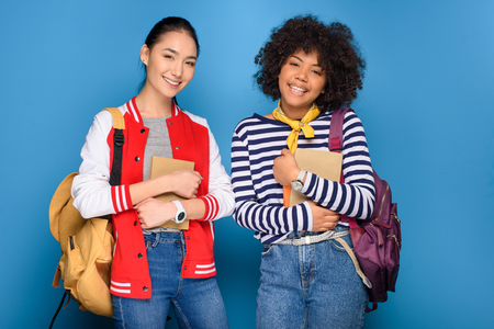 happy female african american and asian students posing with books, isolated on blue