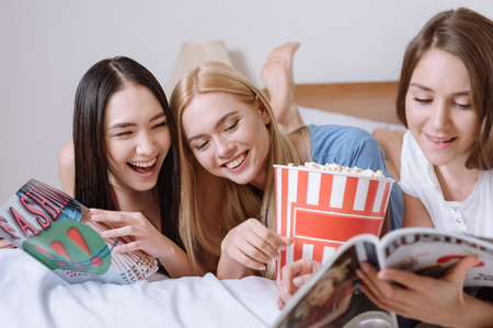smiling multiethnic girls lying on bed with popcorn and reading magazines Foto de archivo