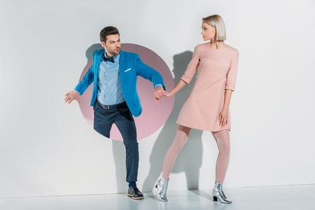 giovane coppia in abito e vestito tenendosi per mano e guardandosi l'un l'altro su gray