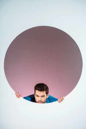 stylish bearded young man looking at camera through hole on grey