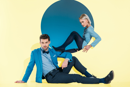 attractive stylish couple sitting and looking at camera on yellow Banque d'images