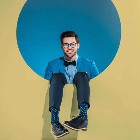 smiling handsome man in fashionable clothes sitting in round beige aperture