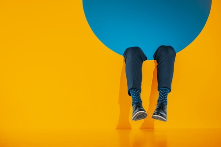 cropped image of male legs in orange round aperture