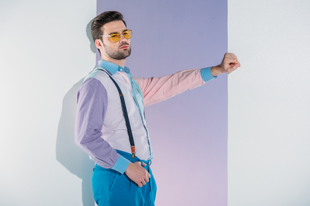 handsome stylish young man in suspenders and eyeglasses leaning at opening on grey