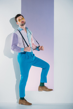 handsome stylish young man in suspenders and eyeglasses standing in aperture on grey 版權商用圖片