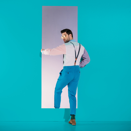 rear view of handsome man in fashionable clothes going through frame on turquoise