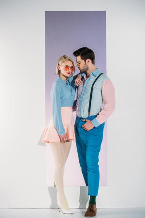 side view of fashionable young couple in sunglasses standing together in opening on grey 版權商用圖片