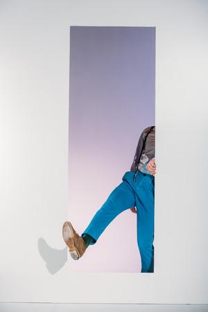 cropped shot of stylish man walking through opening on grey