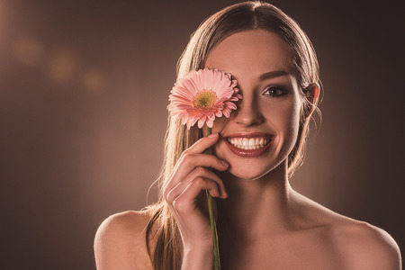 attractive cheerful girl with gerbera flower, on brown 版權商用圖片