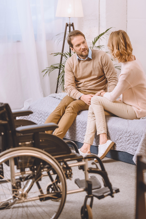 husband with disability and wife sitting and talking on bed Standard-Bild - 114543967