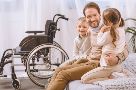 happy father with disability sitting with children on bed Archivio Fotografico