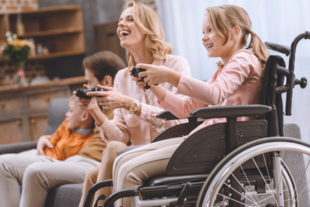 happy family with disabled child in wheelchair playing with joysticks together at home Stock fotó - 114545346