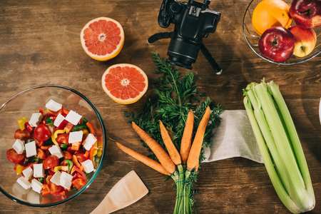 top view of digital camera and vegetables with fruits on wooden table