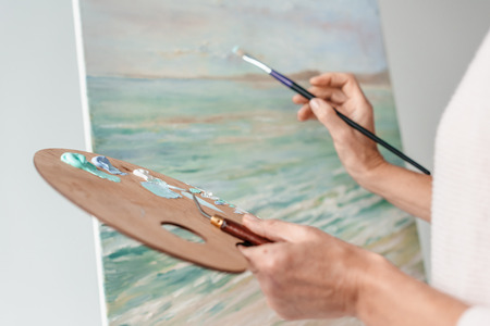 cropped shot of artist holding palette and paintbrush while painting at easel in art studio Stock Photo