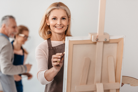 beautiful mature woman smiling at camera while painting on easel at art class 写真素材