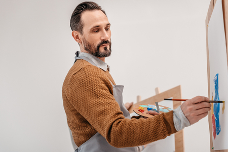 mature male artist holding palette and painting in art studio Banco de Imagens