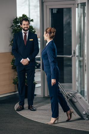 businesswoman going out of hotel luggage and looking at doorman Standard-Bild