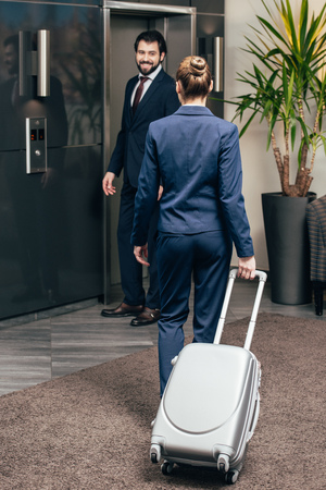 business people with luggage going on elevator together Imagens