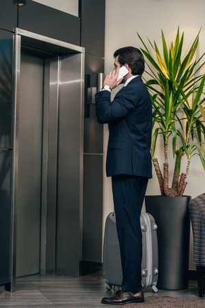 stylish businessman with luggage talking by phone while waiting for elevator at hotel 写真素材