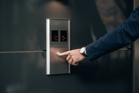 cropped shot of businessman in suit pressing button of elevator