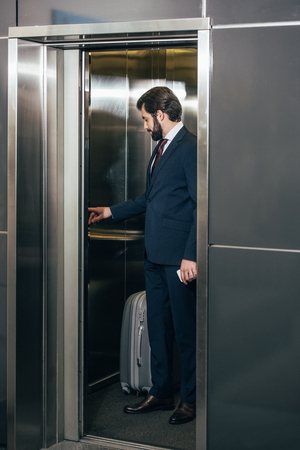 businessman with luggage pressing button inside elevator 版權商用圖片