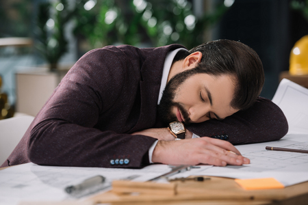 exhausted architect sleeping on building plans at workplace