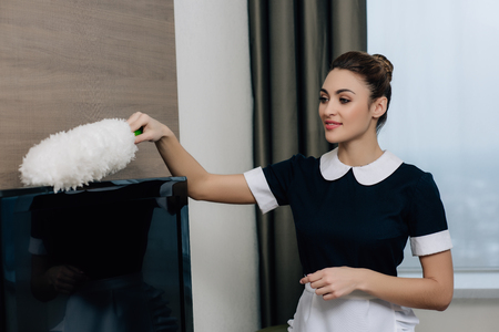 young happy maid in uniform cleaning tv with duster at hotel suite