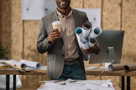 cropped shot of smiling architect with coffee to go and rolled blueprints at workplace